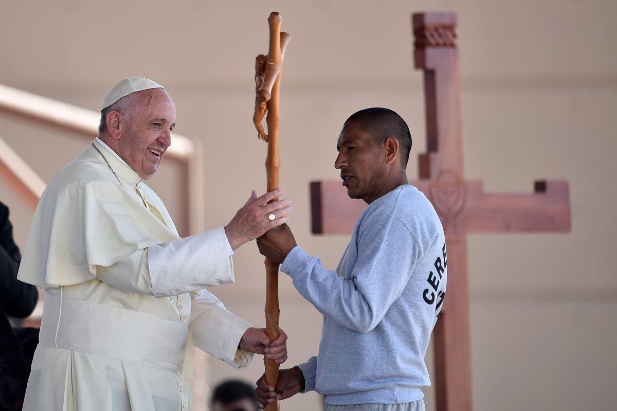 El papa Francisco recibe un crucifico de un reo durante la visita que hizo al penal de Ciudad Juárez. (Foto Prensa Libre: AFP).