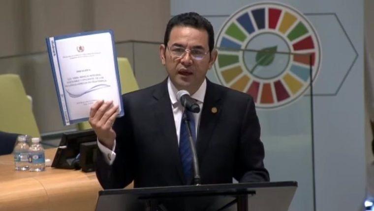 Presidente Jimmy Morales muestra la iniciativa de Ley que presentará al Congreso. (Foto Prensa Libre: Cortesía SCSPR)