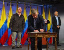 El presidente colombiano Juan Manuel Santos (C), acompañado por el ministro de Defensa Luis Carlos Villegas (i) y el comisionado por la Paz Rodrigo Rivera, firmando el alto el fuego con la guerrilla del ELN. (Foto Prensa Libre:AFP).
