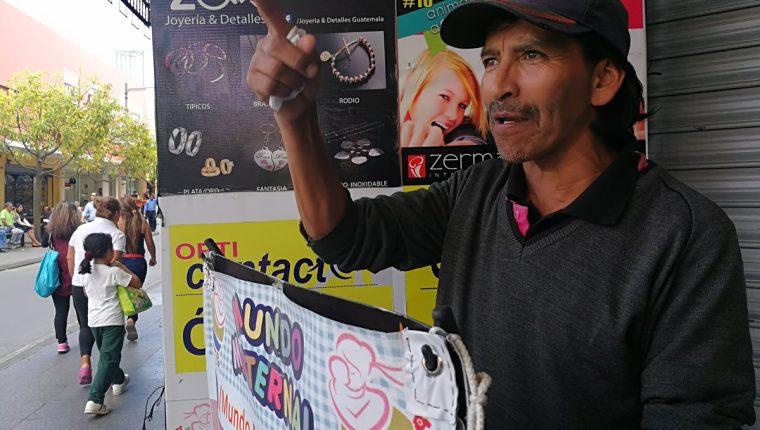 Gustavo Adolfo Juárez Ruiz ofrece ofertas a los visitantes del Paseo de la Sexta, su jornada laboral es de 9 a 16 horas. (Foto Prensa Libre: Edwin Pitán)