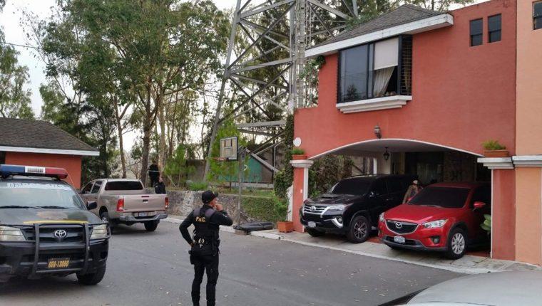 Agentes de la PNC resguardan una de las viviendas allanadas durante operativos del MP y la Cicig en varios puntos de la capital. (Foto Prensa Libre)