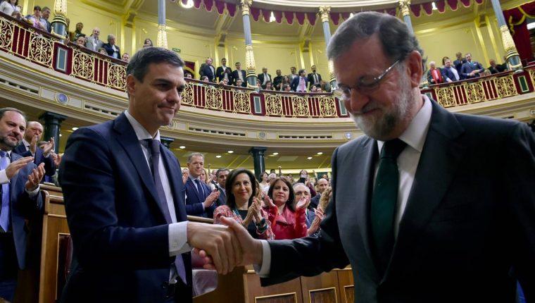 Pedro Sánchez le da un apretón de manos a Mariano Rajoy, luego de cesarlo del cargo. (Foto Prensa Libre: AFP)