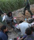 Agentes de la Patrulla Fronteriza vigilan a un grupo de inmigrantes detenidos en un campo de caña cerca de la frontera de EE. UU.-México. (AFP).