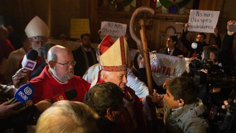 Varias personas se manifiestan contra los obispos que encubrían el abuso sexual en momentos cuando periodistas entrevistan al arzobispo de Santiago, Ricardo Ezzati (C). (AFP)