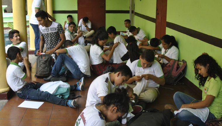 Jóvenes que cursan Básico en el Instituto Simón Bergaño y Villegas reciben clases en los corredores del Centro Cultural Arístides Crespo.(Foto Prensa Libre: Carlos Paredes)