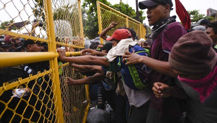 Momento en que las autoridades guatemaltecas intentan evitar el paso de hondureños hacia el puente internacional que divide el país con México. (Foto Prensa Libre: AFP)