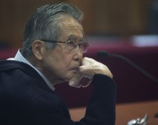 Peru's jailed, former President Alberto Fujimori, photographed through a glass window, attends his trial at a police base on the outskirts of Lima, Peru, Tuesday, June 28, 2016. Fujimori, who is already serving 25 years following previous convictions, is being tried for allegedly diverting government funds to finance newspapers that backed his successful run for a third term. (AP Photo/Martin Mejia)