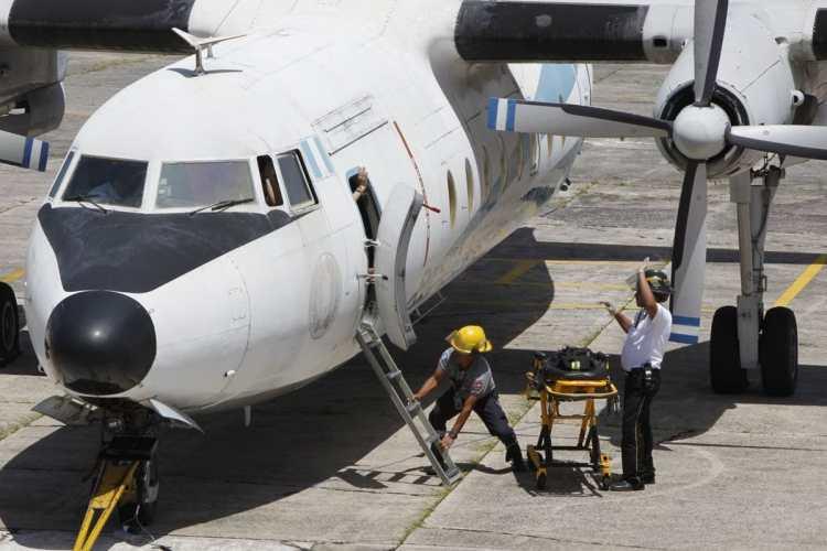 Los cuerpos de socorro sacan a una supuesta víctima del avión, durante el simulacro de secuestro aéreo en el Aeropuerto Internacional La Aurora.
