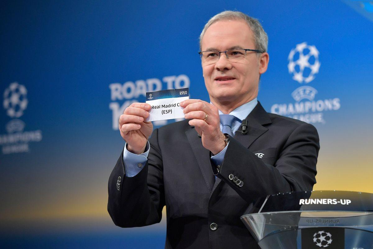 El director de competición de la Uefa, Giorgio Marchetti muestra la papeleta del Real Madrid durante el sorteo de octavos de final de la Champions League. (Foto Prensa Libre: AFP)