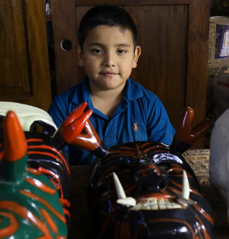 El pequeño Jordi Jesús ayuda en la elaboración de máscaras en el taller de la familia Hernández. (Foto Prensa Libre: Cortesía Victorino Tejaxún)