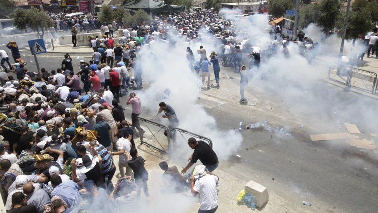 Los palestinos huyen de los gases lacrimógenos lanzados por la policía israelí fuera de la Ciudad Vieja de Jerusalén.(AP).