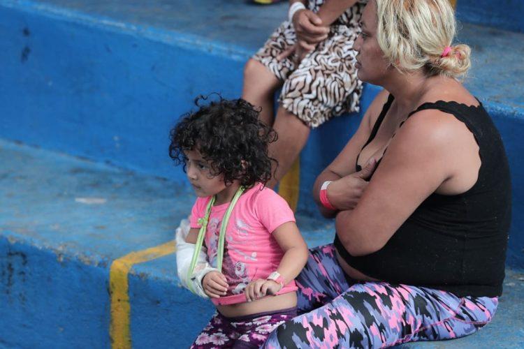 Una niña con su brazo quebrado espera por medicina mientras otro familiar hace la fila para recibirla.