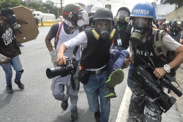 Un periodista es llevado herido por sus compañeros durante una protesta en Venezuela. (Foto: Hemeroteca PL)