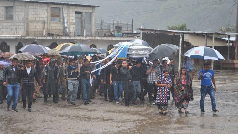 Familiares y amigos trasladan al camposanto los restos del agente Arnoldo Lejá Peneleu. (Foto Prensa Libre: Ángel Julajuj)