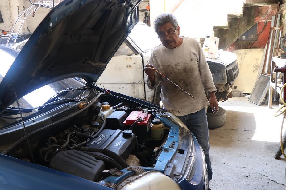 El mecánico José Villagrán recomienda que cuando un carro se inunda es necesario desconectar la batería, revisar la varilla del aceite y los filtros. (Foto Prensa Libre: María José Longo)