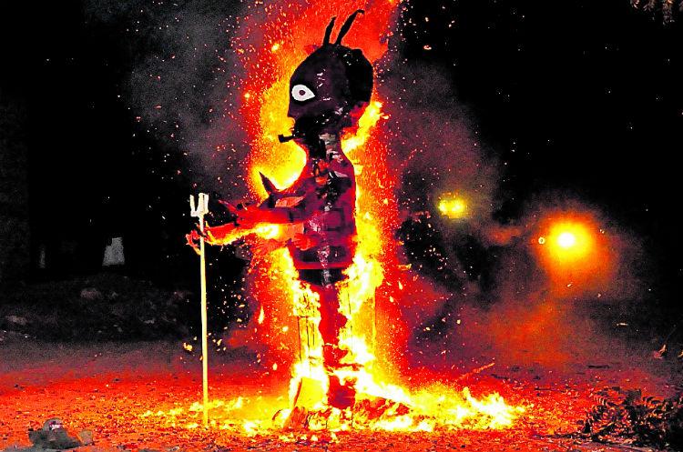 Vecinos del barrio El Zapatillo, Chiquimula, observan la piñata de la imagen de Satanás que es consumida por las llamas.