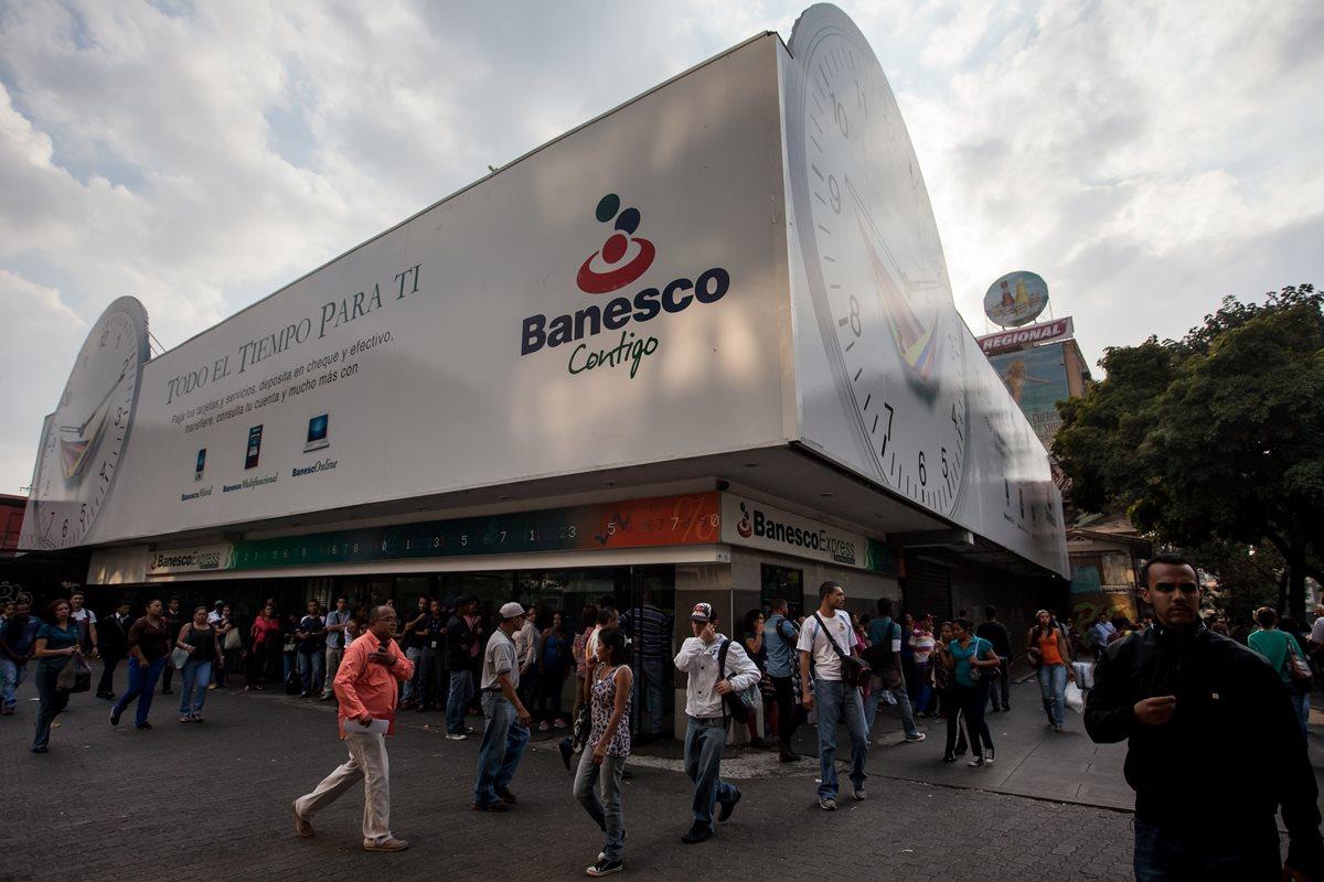 Decenas de personas hacen cola, en vano, en Venezuela, para retirar algo de dinero de cajeros de un conocido banco. (Foto PL: EFE)