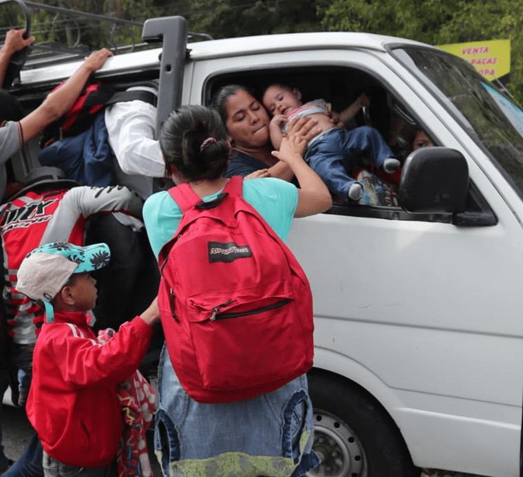 Una mujer le da su bebé a su hermana que logró abordar un microbús en Zacapa. (Foto Prensa Libre: Érick Ávila)