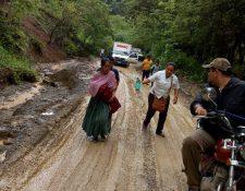 Madre corre junto a enfermera, entre el lodo, pidiendo ayuda a un motociclista para trasladar a su bebé al hospital. (Foto Prensa Libre: Eduardo Sam)