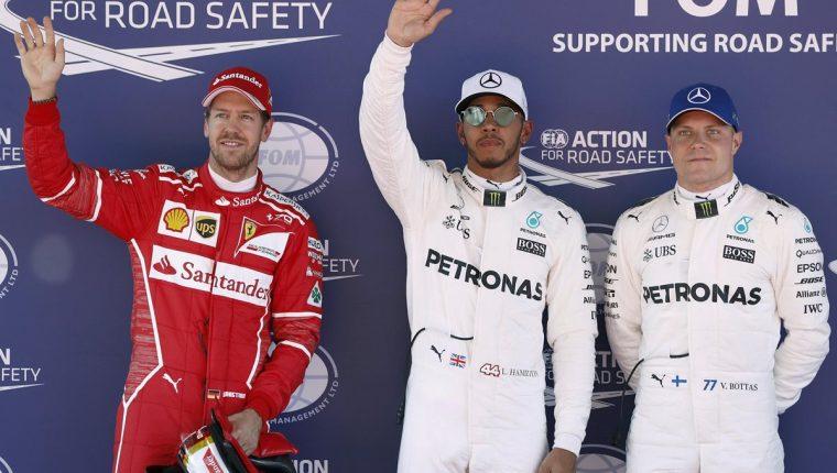 Lewis Hamilton, del equipo Mercedes, celebra la primera posición junto a su compañero de equipo el piloto finlandés Valtteri Bottas y Sebastian Vettel. (Foto Prensa Libre: EFE)