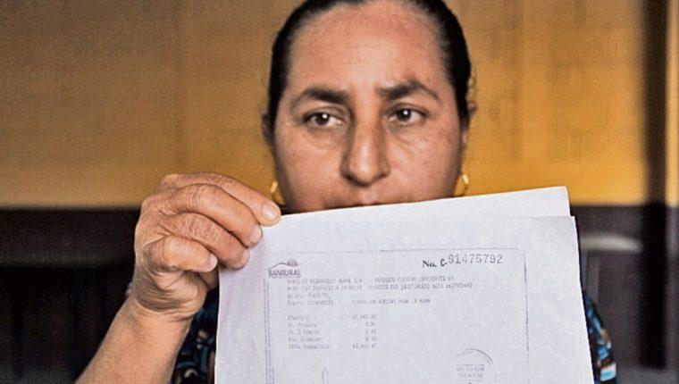Ruby Villatoro muestra la boleta bancaria del pago de su vivienda.