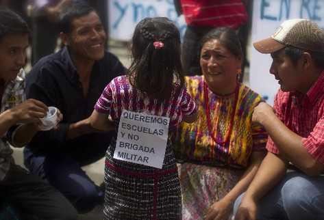Una niña sostiene un cartel con un mensaje contra la instalación de brigada militar en San Juan. (Foto Prensa Libre: EFE)