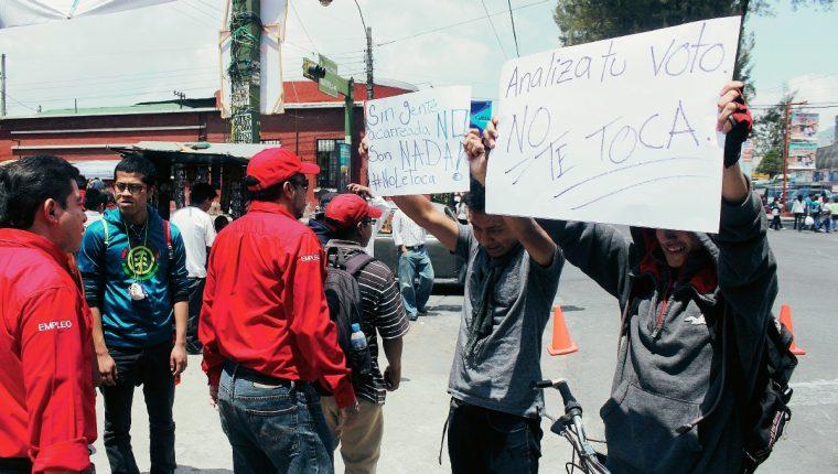 Dos jóvenes piden analizar voto en actividad de Líder, en Quetzaltenango. (Foto Prensa Libre: Carlos Ventura)