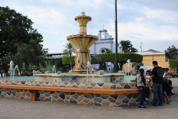Un grupo  de personas  se refresca   en la fuente del parque central de Tecún Umán, San Marcos.