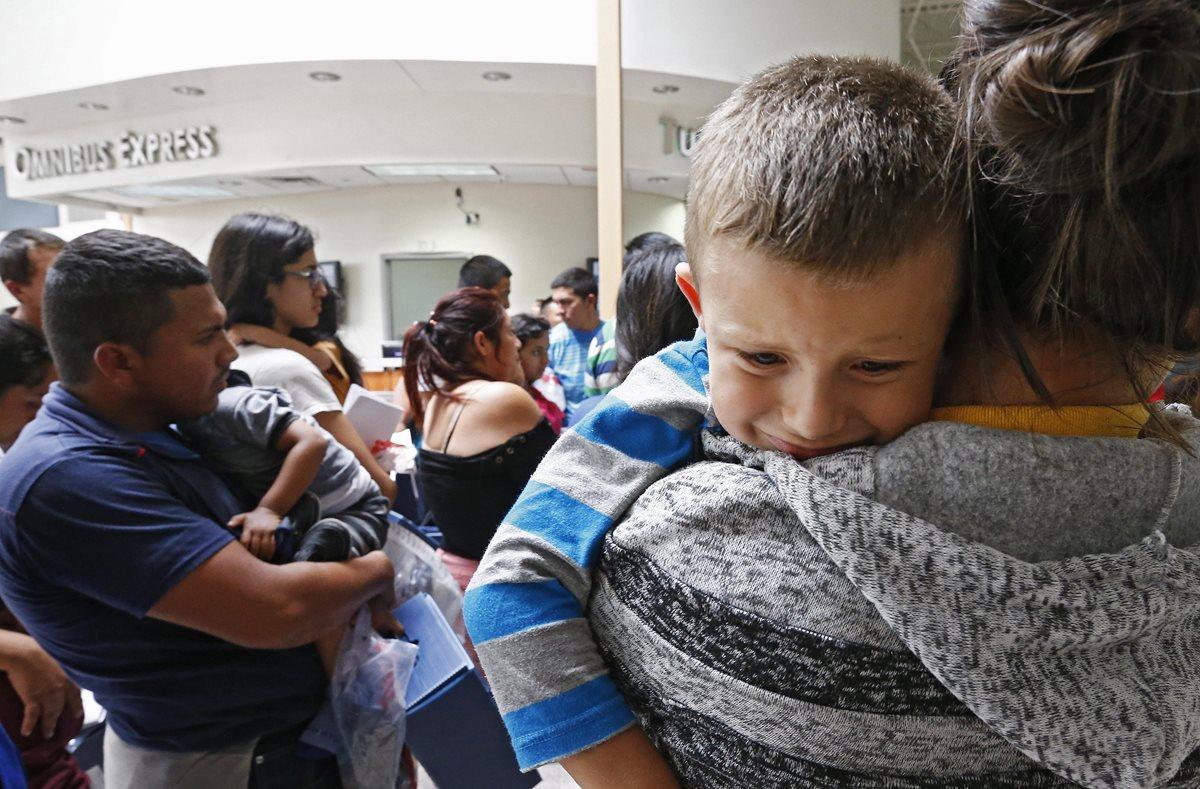Un niño llora mientras su madre espera a ser procesada en un albergue. (Foto Prensa Libre: EFE)