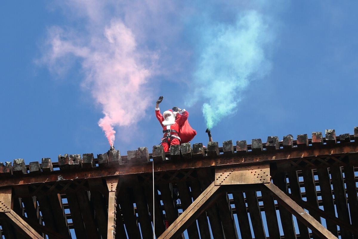 El Santa Claus bombero desciende del puente Las Vacas con una bolsa llena de regalos para niños de las colonias bajo el puente Belice. (Foto Prensa Libre: Esbin García)