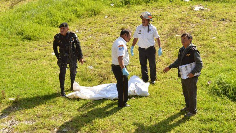 Socorristas y agentes policiales resguardan el cadáver de un joven localizado en la cabecera de Totonicapán. (Foto Prensa Libre: Édgar Domínguez)