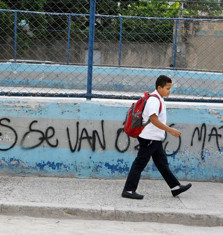 Un estudiante pasa frente a un graffiti hecho por la pandilla Mara Salvatrucha en el barrio El Bosque.(Foto Prensa Libre:AFP).