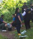 Fiscales del Ministerio Público rsguardan el cadáver del hombre que fue lanzado desde un vehículo en marcha. (Foto Prensa Libre: Óscar González)