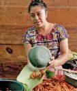 María atiende su venta de mariscos en el mercado de San Pedro La Laguna y dejó de utilizar bolsas de plástico, ahora entrega su producto  en hojas de plátano. (Foto Prensa Libre: EFE)