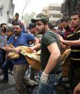 Un grupo de hombres saca de los escombros los restos de una víctima del mortífero atentado en Bagdad. (Foto Prensa Libre: AFP).