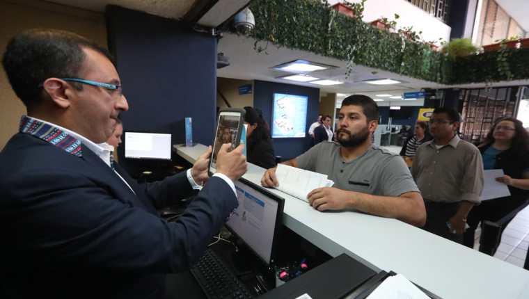 Un empleado de la SAT identifica a una persona y registra en el nuevo sistema de filas su trámite. (Foto Prensa Libre: Mynor Toc)