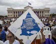 Una mujer sostiene un cartel que pide la paz y el diálogo en la Plaza de la Revolución en Managua, Nicaragua. (Foto Prensa Libre:AFP).
