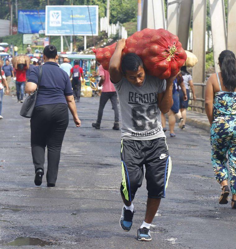 Un comerciante carga su mercadería para pasar por el puente Castillo Armas, en Santa Cruz Muluá, Retalhuleu. (Foto Prensa Libre: Rolando Miranda)