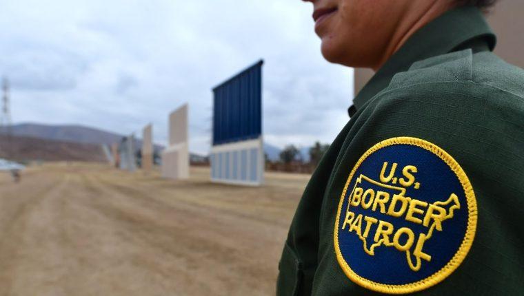 Un oficial de la Patrulla Fronteriza estadounidense se encuentra cerca de los prototipos del muro fronterizo propuesto por Donald Trump en San Diego, California. (Foto Prensa Libre: AFP).