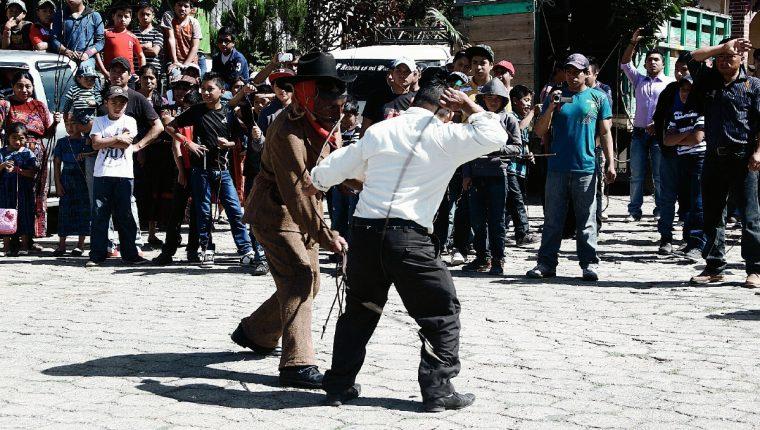 Un hombre  que se disfraza de Judas o Shutío, pelea a latigazos con pobladores en San Andrés Semetabaj, Sololá, para expiar los pecados. (Foto Prensa Libre: Ángel Julajuj)