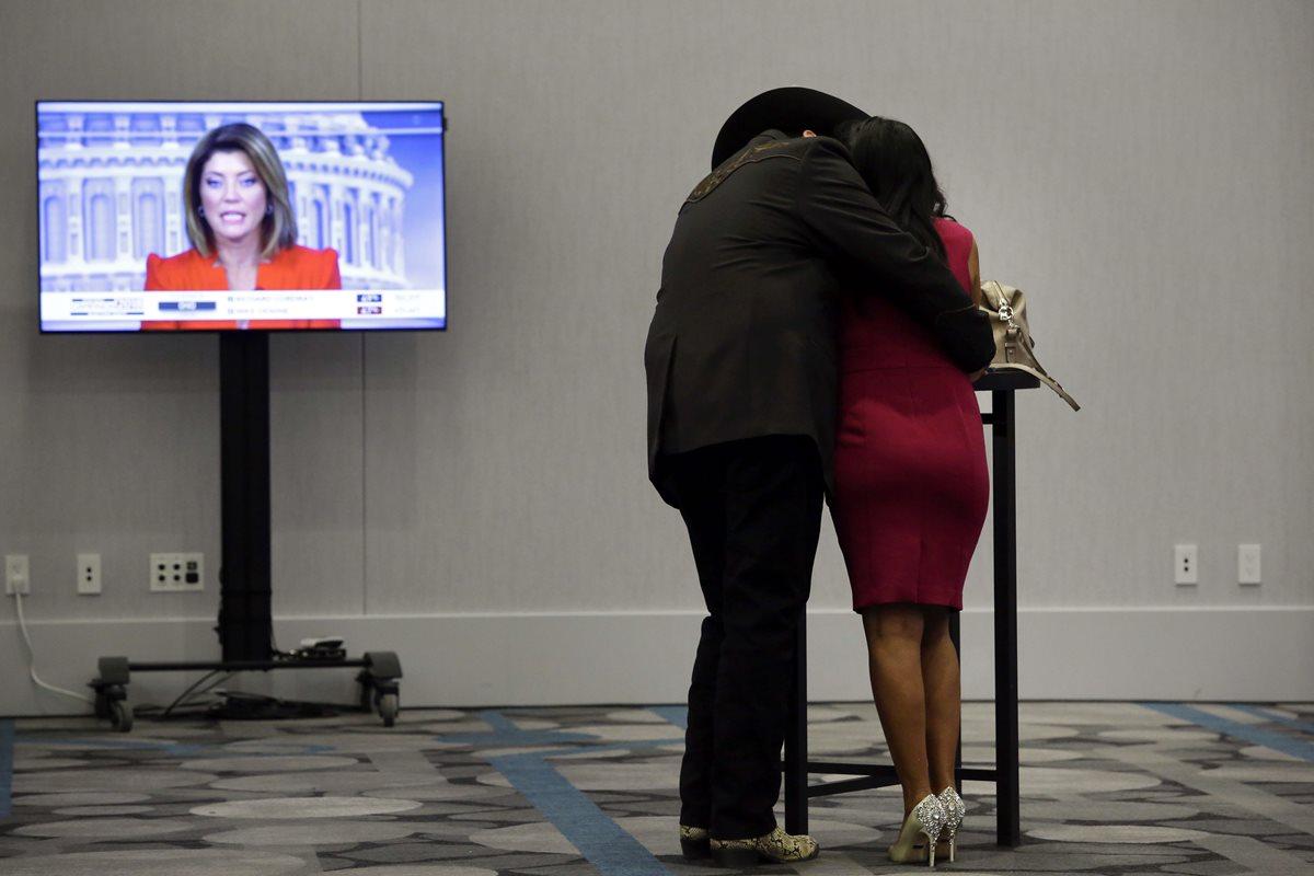 Una pareja espera los resultados observando un monitor en Iowa.