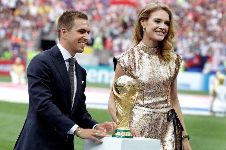El exfutbolista alemán Philipp Lahm y la modelo rusa Natalia Vodianova portan el trofeo del Mundial antes del partido Francia-Croacia