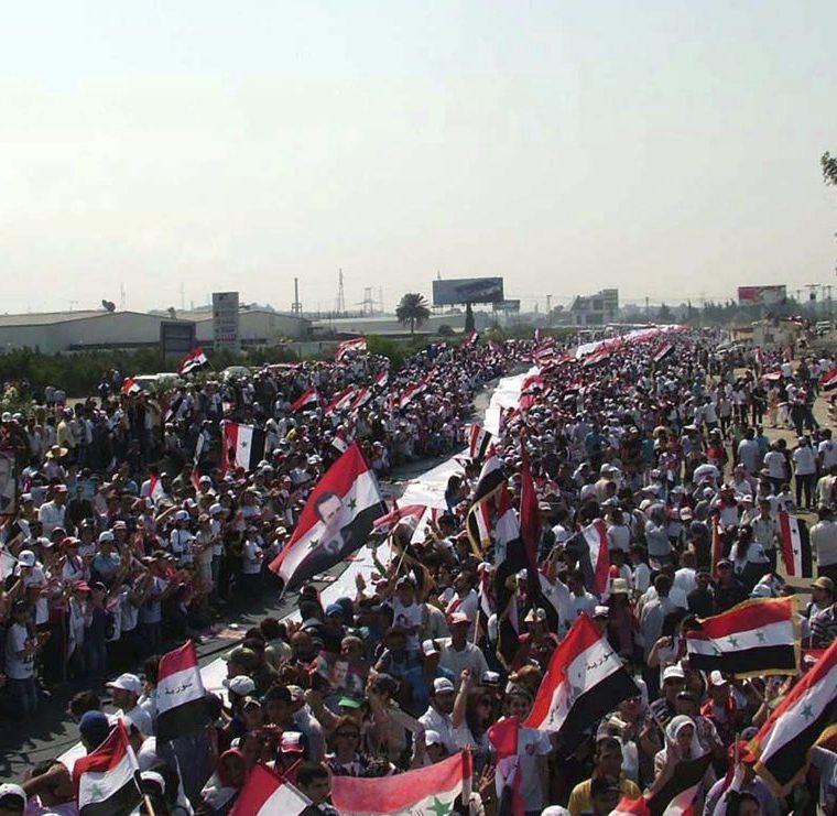 Manifestantes con una bandera nacional de 16 kilómetros en una muestra de apoyo al diálogo nacional convocado por el presidente sirio Bashar al Asad el 10 de julio de 2011 en Latakia, Siria. (Foto: EFE)