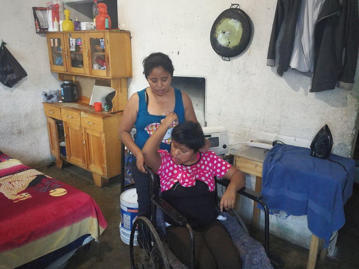 Marina González junto a su hija Wendy, quien permanece en silla de ruedas. (Foto Prensa Libre: Oscar García).