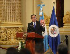 """El presidente Jimmy Morales sostiene una copia del libro """"Fake news: La verdad de las noticias falsas"""" escrito por Marc Amorós García. (Foto Prensa Libre: Erick Ávila)"""