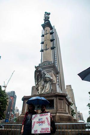 Dos manifestantes exhiben un cartel donde pididen la eliminación de la estatua de Cristóbal Colón en Nueva York. (AFP).