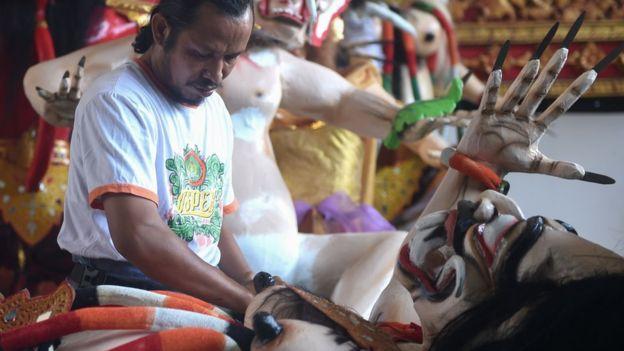 Un hombre prepara las estatuas conocidas como Ogoh-ogoh, que simbolizan el mal. AFP