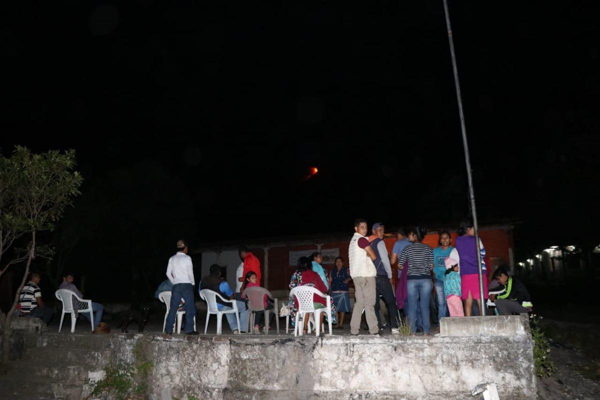 Algunos vecinos observan la erupción a la distancia.