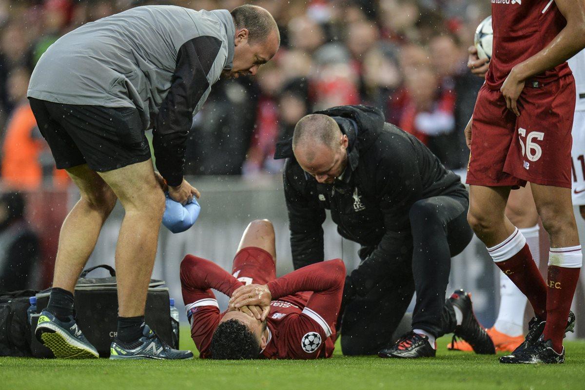 Alex Oxlade-Chamberlain (c) del Liverpool recibe asistencia médica durante el partido de ida de semifinales de la Liga de Campeones. (Foto Prensa Libre: EFE)