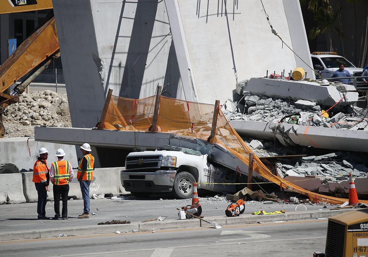 Trabajadores investigan la escena donde un puente peatonal se derrumbó en Miami. (AFP).
